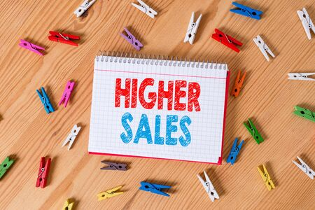 Conceptual hand writing showing Higher Sales. Concept meaning The average sold products and services of a company has grown Colored crumpled papers wooden floor background clothespin