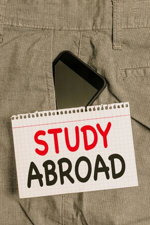 Handwriting text Study Abroad. Conceptual photo Pursuing educational opportunities in a foreign country Smartphone device inside formal work trousers front pocket near note paper