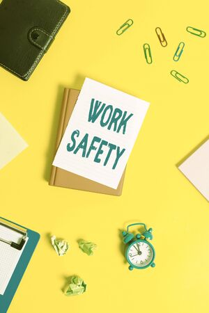 Text sign showing Work Safety. Business photo showcasing Policies and control in place according to government standard Pile of empty papers with copy space on the table
