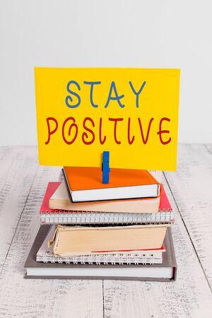 Conceptual hand writing showing Stay Positive. Concept meaning Engage in Uplifting Thoughts Be Optimistic and Real pile stacked books notebook pin color reminder white wooden Stock fotó