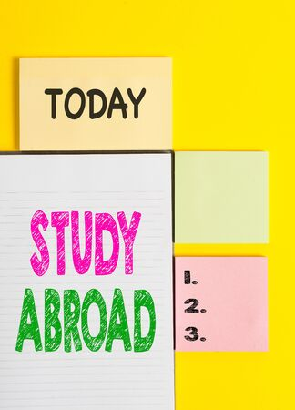 Word writing text Study Abroad. Business photo showcasing Pursuing educational opportunities in a foreign country Colored empty papers with copy space on the yellow background table Фото со стока