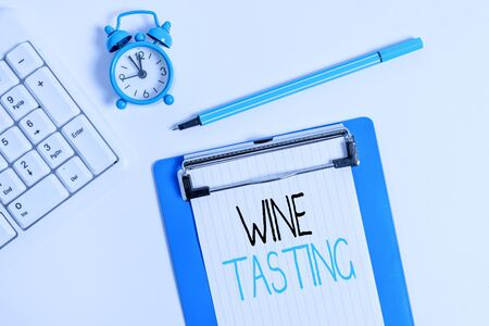 Conceptual hand writing showing Wine Tasting. Concept meaning Degustation Alcohol Social gathering Gourmet Winery Drinking Flat lay above table with clock pc keyboard and note paper