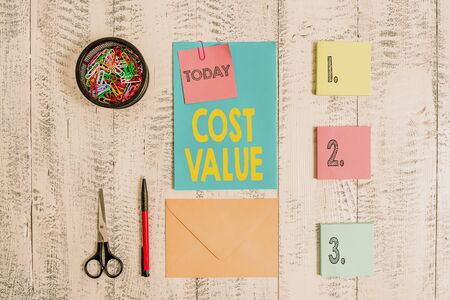 Word writing text Cost Value. Business photo showcasing The amount that usualy paid for a item you buy or hiring a demonstrating Envelope letter sticky note ballpoint clips can scissors wooden background