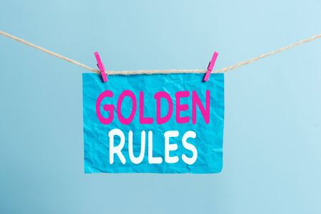 Writing note showing Golden Rules. Business concept for Basic principle that should be followed Important Principle Clothesline clothespin rectangle shaped paper reminder white wood desk
