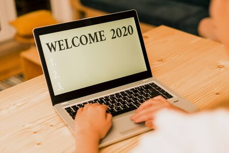 Word writing text Welcome 2020. Business photo showcasing New Year Celebration Motivation to Start Cheers Congratulations woman laptop computer smartphone mug office supplies technological devices