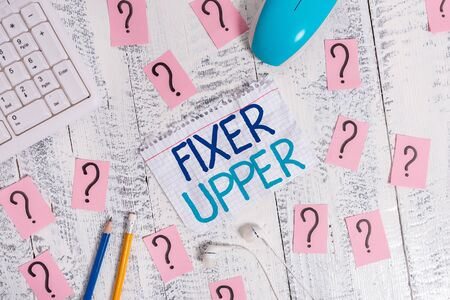 Writing note showing Fixer Upper. Business concept for house in need of repairs used chiefly connection with purchase Writing tools and scribbled paper on top of the wooden table