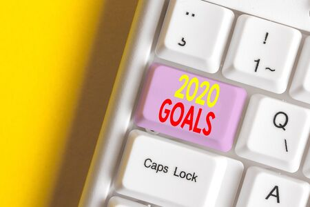 Word writing text 2020 Goals. Business photo showcasing A plan to do for something new and better for the coming year White pc keyboard with empty note paper above white background key copy space Stock Photo