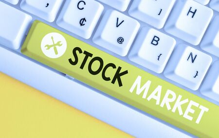 Conceptual hand writing showing Stock Market. Concept meaning Particular market where stocks and bonds are traded or exhange White pc keyboard with note paper above the white background Banco de Imagens