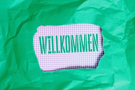 Text sign showing Willkommen. Business photo showcasing welcoming showing event or your home something to that effect Green crumpled ripped colored paper sheet centre torn colorful background