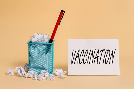 Text sign showing Vaccination. Business photo showcasing Treatment which makes the body stronger against infection crumpled paper trash and stationary with note paper placed in the trash can Stok Fotoğraf
