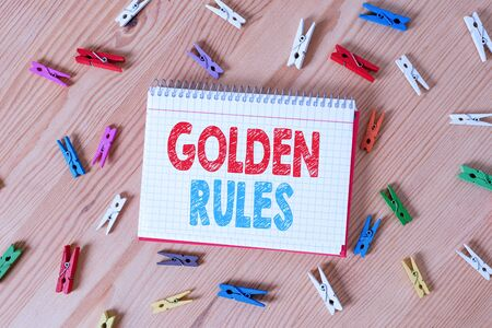Conceptual hand writing showing Golden Rules. Concept meaning Basic principle that should be followed Important Principle Colored crumpled papers wooden floor background clothespin