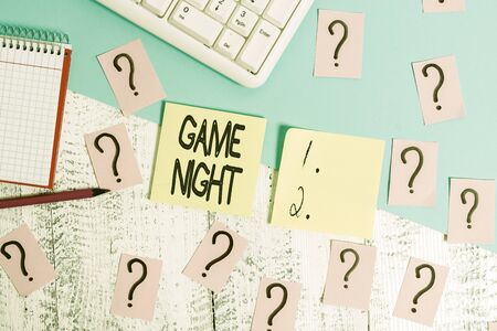 Conceptual hand writing showing Game Night. Concept meaning event in which folks get together for the purpose of getting laid Writing tools and scribbled paper on top of the wooden table
