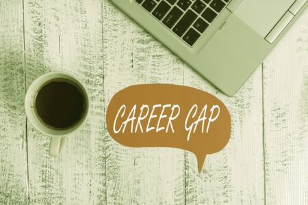 Word writing text Career Gap. Business photo showcasing A scene where in you stop working by your profession for a while Trendy metallic open laptop speech bubble vintage wooden table coffee cup