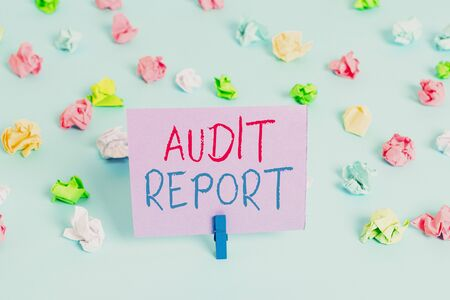 Word writing text Audit Report. Business photo showcasing An appraisal of complete financial status of a business Assets Colored crumpled papers empty reminder blue floor background clothespin