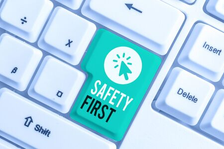 Writing note showing Safety First. Business concept for Avoid any unnecessary risk Live Safely Be Careful Pay attention White pc keyboard with note paper above the white background