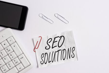 Text sign showing Seo Solutions. Business photo showcasing Search Engine Result Page Increase Visitors by Rankings White pc keyboard with empty note paper above white background and mobile phone Stock Photo