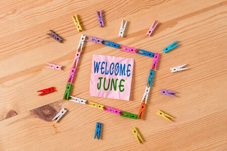Text sign showing Welcome June. Business photo showcasing Calendar Sixth Month Second Quarter Thirty days Greetings Colored clothespin papers empty reminder wooden floor background office
