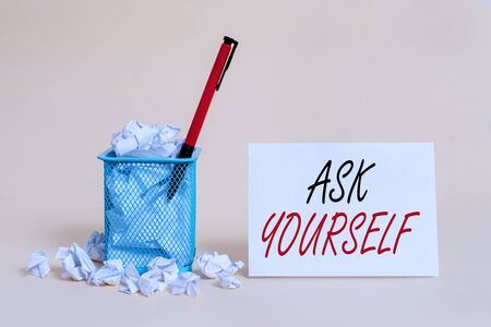 Text sign showing Ask Yourself. Business photo showcasing Thinking the future Meaning and Purpose of Life Goals crumpled paper trash and stationary with note paper placed in the trash can