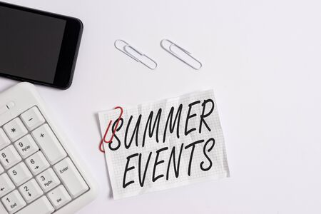 Text sign showing Summer Events. Business photo showcasing Celebration Events that takes place during summertime White pc keyboard with empty note paper above white background and mobile phone Foto de archivo - 130153217