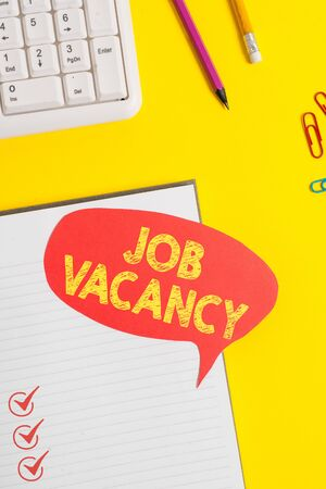 Text sign showing Job Vacancy. Business photo showcasing empty or available paid place in small or big company Pink empty paper on the yellow table with pencil