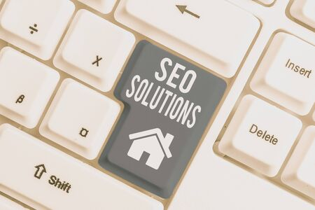 Conceptual hand writing showing Seo Solutions. Concept meaning Search Engine Result Page Increase Visitors by Rankings White pc keyboard with note paper above the white background