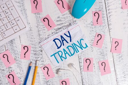 Writing note showing Day Trading. Business concept for securities specifically buying and selling financial instruments Writing tools and scribbled paper on top of the wooden table