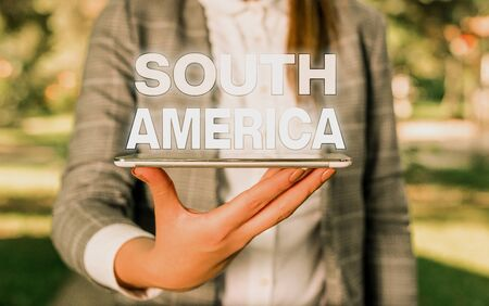 Word writing text South America. Business photo showcasing Continent in Western Hemisphere Latinos known for Carnivals Outdoor scene with business woman holds lap top with touch screen