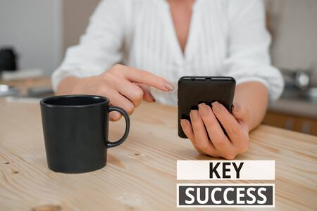 Text sign showing Key Success. Business photo showcasing generally three to five areas that company may focus on woman using smartphone office supplies technological devices inside home 写真素材