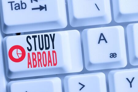 Conceptual hand writing showing Study Abroad. Concept meaning Pursuing educational opportunities in a foreign country Keyboard with note paper on white background key copy space