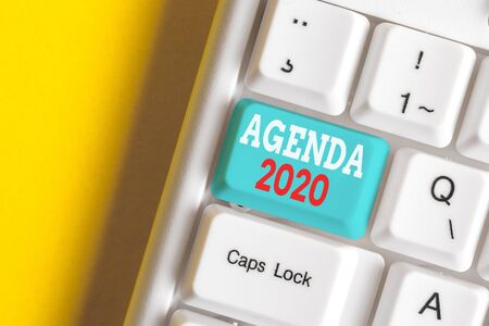 Writing note showing Agenda 2020. Business concept for list of activities in order which they are to be taken up White pc keyboard with note paper above the white background