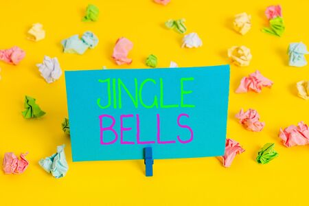 Writing note showing Jingle Bells. Business concept for Most famous traditional Christmas song all over the world Colored crumpled paper empty reminder white floor clothespin 写真素材