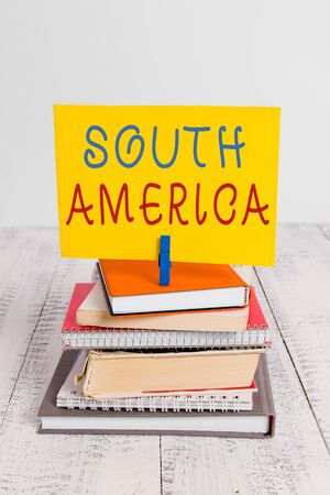Conceptual hand writing showing South America. Concept meaning Continent in Western Hemisphere Latinos known for Carnivals pile stacked books notebook pin color reminder white wooden