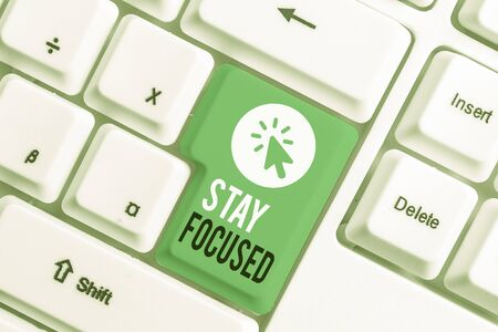 Writing note showing Stay Focused. Business concept for Be attentive Concentrate Prioritize the task Avoid distractions White pc keyboard with note paper above the white background