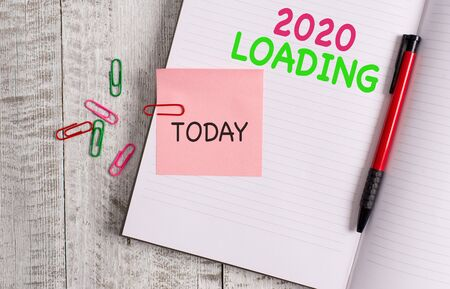 Handwriting text 2020 Loading. Conceptual photo Advertising the upcoming year Forecasting the future event Thick pages notebook stationary placed above classic look wooden backdrop