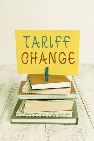Conceptual hand writing showing Tariff Change. Concept meaning Amendment of Import Export taxes for goods and services pile stacked books notebook pin color reminder white wooden