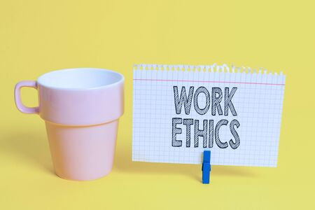 Writing note showing Work Ethics. Business concept for A set of values centered on the importance of doing work Cup empty paper blue clothespin rectangle shaped reminder yellow office