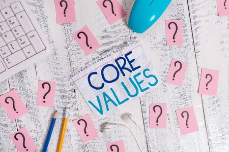 Writing note showing Core Values. Business concept for belief demonstrating or organization views as being importance Writing tools and scribbled paper on top of the wooden table