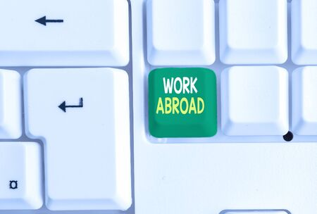 Conceptual hand writing showing Work Abroad. Concept meaning Immersed in a foreign work environment Job Overseas Non Local White pc keyboard with note paper above the white background
