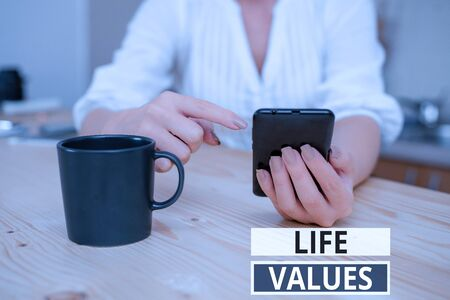 Text sign showing Life Values. Business photo showcasing things that you believe are important in the way you live woman using smartphone office supplies technological devices inside home Banco de Imagens