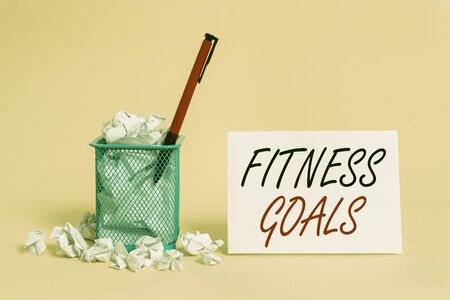 Text sign showing Fitness Goals. Business photo showcasing Loose fat Build muscle Getting stronger Conditioning crumpled paper trash and stationary with note paper placed in the trash can