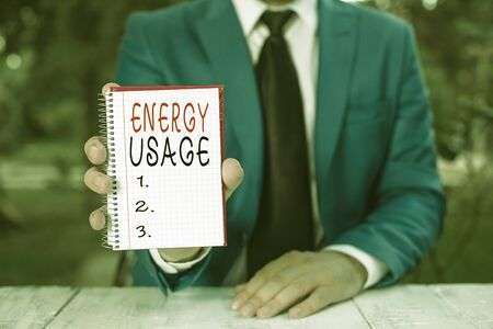 Text sign showing Energy Usage. Business photo text Amount of energy consumed or used in a process or system Man holds empty paper with copy space in front of him