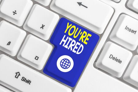 Writing note showing You Re Hired. Business concept for New Job Employed Newbie Enlisted Accepted Recruited White pc keyboard with note paper above the white background