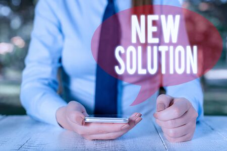 Writing note showing New Solution. Business concept for Modern Innovation Latest effective approach to a problem Female business person sitting by table and holding mobile phone Stock fotó