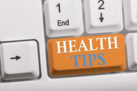 Writing note showing Health Tips. Business concept for state of complete physical mental and social well being White pc keyboard with note paper above the white background