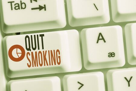 Conceptual hand writing showing Quit Smoking. Concept meaning Discontinuing or stopping the use of tobacco addiction Keyboard with note paper on white background key copy space