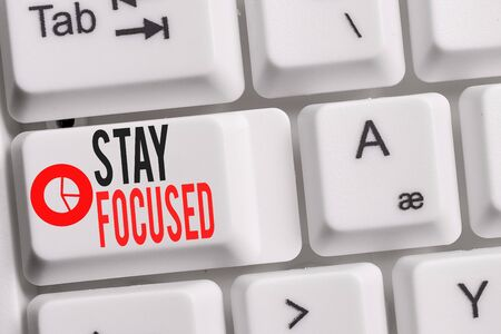 Conceptual hand writing showing Stay Focused. Concept meaning Be attentive Concentrate Prioritize the task Avoid distractions Keyboard with note paper on white background key copy space