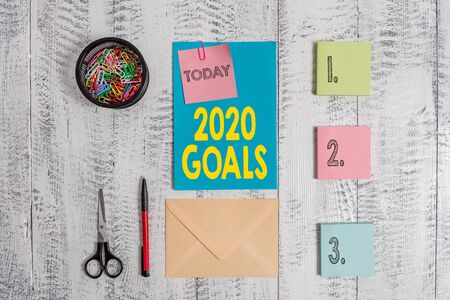Word writing text 2020 Goals. Business photo showcasing A plan to do for something new and better for the coming year Envelope letter sticky note ballpoint clips can scissors wooden background
