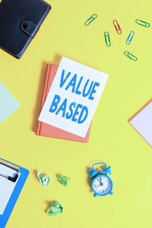 Text sign showing Value Based. Business photo showcasing Considering the product worth in satisfying the customer Pile of empty papers with copy space on the table