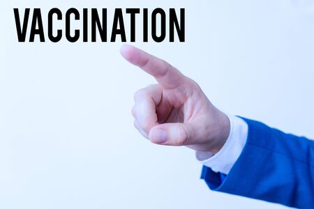 Writing note showing Vaccination. Business concept for Treatment which makes the body stronger against infection Isolated hand pointing with finger. Business concept pointing finger