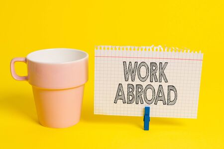 Writing note showing Work Abroad. Business concept for Immersed in a foreign work environment Job Overseas Non Local Cup empty paper blue clothespin rectangle shaped reminder yellow office